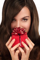 Beautiful woman looking in the camera holding a Christmas gift - PhotoDune Item for Sale