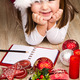 Funny girl in Santa hat writes letter to Santa near christmas decoration  - PhotoDune Item for Sale