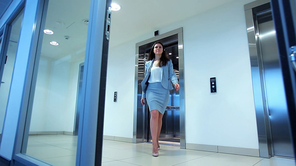 Young Woman Out of the Elevator in Office Building