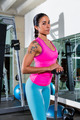 brunette girl with barbell posing at gym - PhotoDune Item for Sale