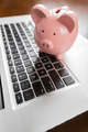 Piggy Bank Resting on Laptop Computer Keyboard. - PhotoDune Item for Sale