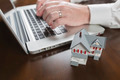 Miniature House Near Male Hands Typing on Laptop Computer. - PhotoDune Item for Sale