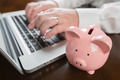 Piggy Bank Near Male Hands Typing on Laptop Computer. - PhotoDune Item for Sale