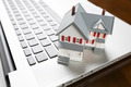 Miniature House And Laptop Computer Resting on Desktop. - PhotoDune Item for Sale