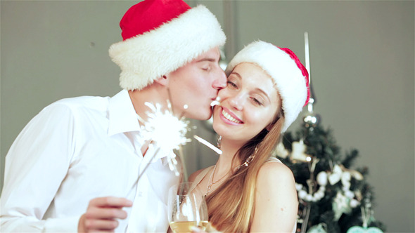 VideoHive Beautiful Couple In Santa Hat Holding Sparklers 9713478