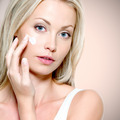 Beautiful woman applying cream on face - PhotoDune Item for Sale