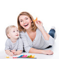 Happy mother playing with little child lying. - PhotoDune Item for Sale