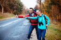 Couple of young backpackers hitchhiking - PhotoDune Item for Sale