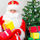 Santa Claus with gifts near the Christmas tree. - PhotoDune Item for Sale