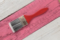 Paint brush on a white  and pink wooden board - PhotoDune Item for Sale
