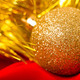 Christmas golden ball and tinsel on red. macro - PhotoDune Item for Sale