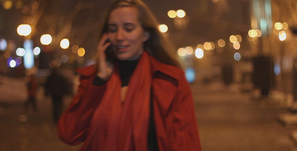 Girl Speaks by Phone in the Evening on the Street