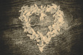 A heart from petals lying on a wooden table - PhotoDune Item for Sale