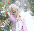 Happy family mother and child playing with christmas tree decoration outdoor - PhotoDune Item for Sale