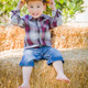 Cute Young Mixed Race Boy Laughing with Hard Hat Outside Sitting on Hay Bale. - PhotoDune Item for Sale