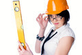 Young female worker with protection helmet and level over isolated background - PhotoDune Item for Sale