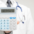 Doctor holding in his hand calculator - health care concept - PhotoDune Item for Sale
