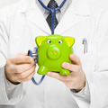 Doctor holding stethoscope and piggybank in hand - medical aid concept - PhotoDune Item for Sale