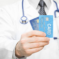 Doctor holding two credit cards in his hand - health care concept - PhotoDune Item for Sale