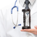 Doctor holdling in his hand a hourglass - healthcare concept - PhotoDune Item for Sale