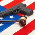 Wooden judge gavel and gun over USA flag - self-defense law concept - PhotoDune Item for Sale