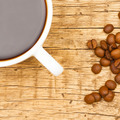 Close up of neat coffee cup with roasted coffee beans on wooden table - view from top - PhotoDune Item for Sale