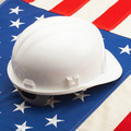 White color construction helmet laying over US flag - construction industry concept - PhotoDune Item for Sale