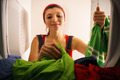 Woman Doing Housekeeping Taking Dry Clothes From Dryer At Home - PhotoDune Item for Sale