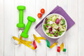 Dumbells, tape measure and healthy food