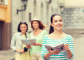 smiling teenage girls with city guides and camera - PhotoDune Item for Sale