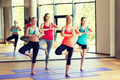 smiling women meditating on mat in gym - PhotoDune Item for Sale