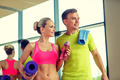 smiling couple with water bottles in gym - PhotoDune Item for Sale