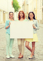 smiling teenage girls with blank billboard - PhotoDune Item for Sale