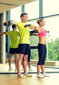 smiling man and woman with dumbbells in gym - PhotoDune Item for Sale