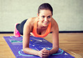 smiling woman doing exercises on mat in gym - PhotoDune Item for Sale