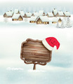 Winter holiday christmas background with a village, a sign and a santa hat.  - PhotoDune Item for Sale