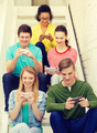 smiling students with smartphone texting at school - PhotoDune Item for Sale