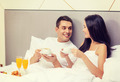 smiling couple having breakfast in bed in hotel - PhotoDune Item for Sale