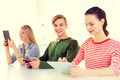 smiling students with tablet pc at school - PhotoDune Item for Sale