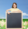 happy little girl pointing finger to blackboard - PhotoDune Item for Sale
