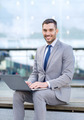 smiling businessman working with laptop outdoors - PhotoDune Item for Sale