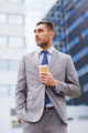 young serious businessman with paper cup outdoors - PhotoDune Item for Sale