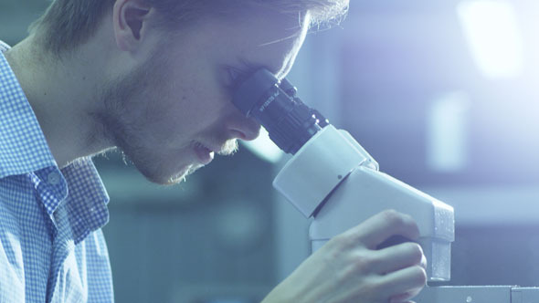 Engineer Inspects Detail Quality under Microscope