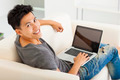 young Man sitting in sofa and using  laptop - PhotoDune Item for Sale