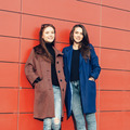 Two beautiful young girl friends in  coats posing near red wall  - PhotoDune Item for Sale