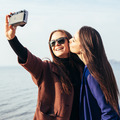Two girlfriends doing selfie on the beach in front of the sea - PhotoDune Item for Sale