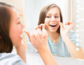 Beauty teenage girl flossing her teeth at home. Dental hygiene - PhotoDune Item for Sale