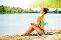 Beautiful girl applying sun tan cream on her skin on the beach - PhotoDune Item for Sale