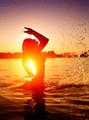 Teen girl swimming and splashing on summer beach over sunset - PhotoDune Item for Sale