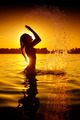 Teen girl swimming and splashing on summer beach over sunset - PhotoDune Item for Sale
